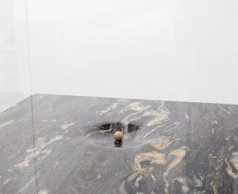 Gabriel Leger, L'Obole, 2018. Bille de pierre (Néolithique), granit, capot de verre, socle 53 x 53 x 50 cm + socle (détail). Courtesy Gabriel Leger et Galerie Sator, Paris.